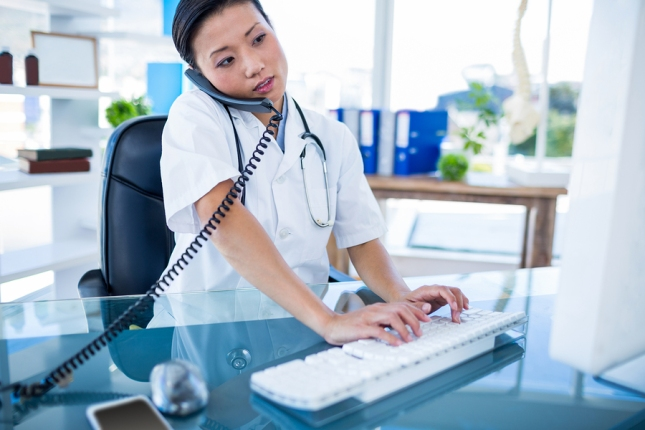 Doctor having phone call and using her computer in medical offic